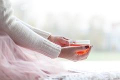 Femme dans un chandail gris et des chaussettes chaudes tenant une tasse de thé tout en se reposant sur un blanc tricotait la couv Photographie stock libre de droits