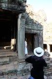 Femme dans un chapeau blanc et regards noirs de chandail aux ruines antiques Une femme examine photo libre de droits