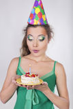 Femme dans un chapeau d'anniversaire soufflant la bougie sur le gâteau Photo stock