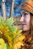 Femme dans un chapeau jaune avec des lames en automne photo stock