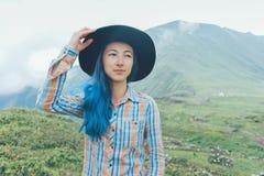 Femme dans un chapeau marchant dans les montagnes Image stock