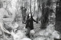 Femme dans un costume de sorcière dans une forêt dense photos libres de droits