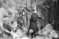 Femme dans un costume de sorcière dans une forêt dense images libres de droits