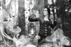 Femme dans un costume de sorcière dans une forêt dense photos stock