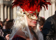 Femme dans un costume et masque avec les plumes rouges au carnaval à Venise, Italie Photos stock