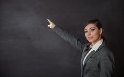 Femme dans un costume montrant le tableau noir Image stock