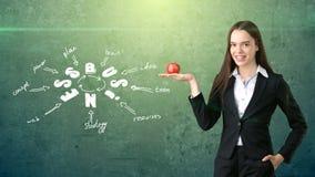Femme dans un costume tenant la pomme rouge tenant le mur proche avec le croquis d'idée d'affaires dessiné là-dessus Concept des  Photos stock
