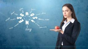 Femme dans un costume tenant la pomme rouge tenant le mur proche avec le croquis d'idée d'affaires dessiné là-dessus Concept des  Photos libres de droits