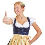 Femme dans un dirndl tenant des pouces  Photos libres de droits