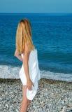 Femme dans un essuie-main sur une plage Photo stock