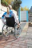 Femme dans un fauteuil roulant sur une rampe de fauteuil roulant photo libre de droits