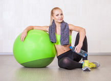 Femme dans un gymnase se reposant après la formation avec la boule de forme physique Photos stock