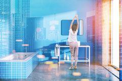 Femme dans un intérieur bleu de salle de bains modifié la tonalité Image stock