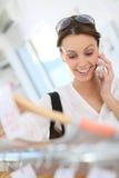 Femme dans un magasin d'habillement choisissant des vêtements et parlant au téléphone Image stock
