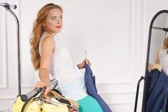Femme dans un magasin d'habillement essayant sur le miroir photographie stock