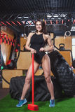 Femme dans un maillot de bain noir tenant un marteau rouge images stock