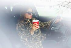 Femme dans un manteau de fourrure avec les lèvres rouges avec du café pour aller la conduire Images stock