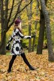 Femme dans un manteau et un chapeau modelés floraux de vin rouge en parc, par la rivière Fille heureuse, portrait coloré de forêt Images libres de droits