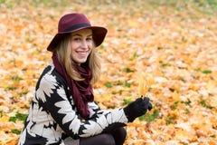 Femme dans un manteau et un chapeau modelés floraux de vin rouge en parc, par la rivière Fille heureuse, portrait coloré de forêt Photos stock