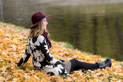 Femme dans un manteau et un chapeau modelés floraux de vin rouge en parc, par la rivière Fille heureuse, portrait coloré de forêt Photo stock