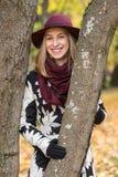 Femme dans un manteau et un chapeau modelés floraux de vin rouge en parc, par la rivière Fille heureuse, portrait coloré de forêt Photographie stock