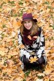 Femme dans un manteau et un chapeau modelés floraux de vin rouge en parc, par la rivière Fille heureuse, portrait coloré de forêt Photographie stock libre de droits