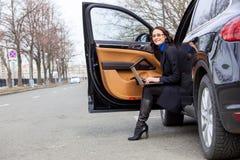 Femme dans un manteau foncé se reposant au seuil de la voiture Photo stock