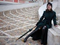 Femme dans un manteau vert posant sur des escaliers Photo libre de droits