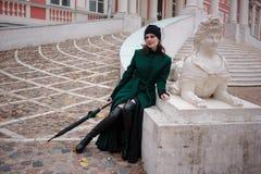 Femme dans un manteau vert posant sur des escaliers Images libres de droits