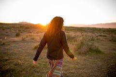 Femme dans un paysage immaculé pendant un beau coucher du soleil de flambage images libres de droits