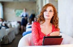 Femme dans un restaurant avec le menu dans des mains Photographie stock libre de droits