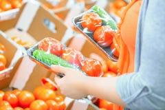 Femme dans un supermarché aux achats végétaux d'étagère pour des tomates et des concombres Concept d'achats Photographie stock libre de droits