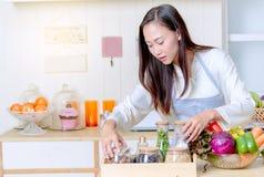 femme dans un tablier faisant cuire la nourriture saine dans la cuisine Photographie stock libre de droits
