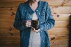 Femme dans un witn de laine de chandail par tasse de thé chaud Image stock