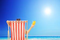 Femme dans une chaise longue appréciant le soleil avec un cocktail dans elle Photo stock
