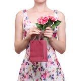Femme dans une impression florale de robe dans les roses rouges de fleur de paquet de sac de mains image stock