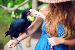 Femme dans une jungle tropicale avec l'oiseau tropical sur la main dans Bali Images libres de droits