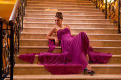 Femme dans une longue robe se trouvant sur les escaliers Image stock