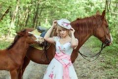 Femme dans une rétro robe avec des chevaux Image stock