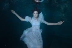 Femme dans une robe blanche sous l'eau photos libres de droits