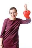 Femme dans une robe de Bourgogne qui rit tenant le coeur dans sa main photo stock