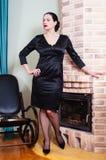 Femme dans une robe de soirée noire tenant la cheminée proche Image stock