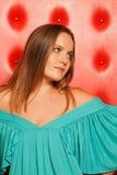 Femme dans une robe de turquoise, près de à mur rouge images stock