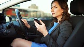 Femme dans une robe et une veste bleues utilisant un smartphone dans la voiture clips vidéos