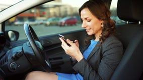 Femme dans une robe et une veste bleues utilisant un smartphone dans la voiture banque de vidéos