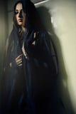 Femme dans une robe longue noire au mur vert photos stock