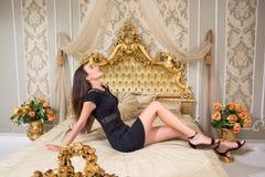 Femme dans une robe noire courte reposant un lit luxueux Photo stock