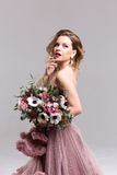 Femme dans une robe rose avec le bouquet de fleur Photo libre de droits