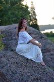 Femme dans une séance blanche de robe Photographie stock