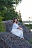 Femme dans une séance blanche de robe Photos stock
